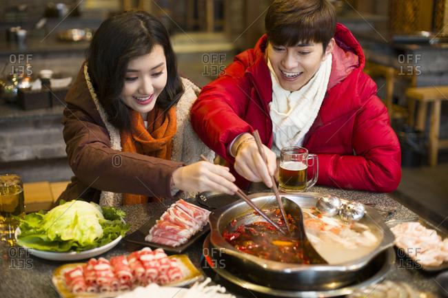 Young couple having dinner in hotpot restaurant