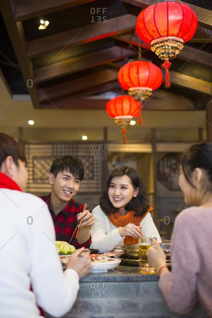Young friends having dinner in hotpot restaurant