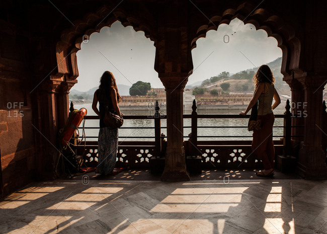 Rajasthan, India - November 5, 2015: Two girls overlook Amber Fort view from Lake Maoth framed in Indian Arches.