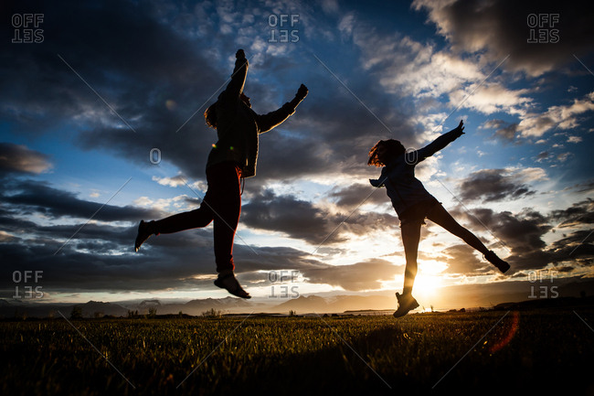 Two girls leap through the air backlit by a dramatic mountain sunset in Iceland