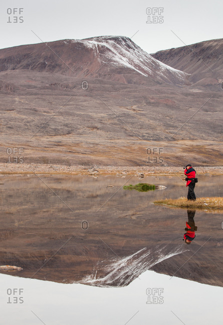 Ellesmere Island, Canada - August 25, 2016: A man taking a picture of the landscape and his reflection
