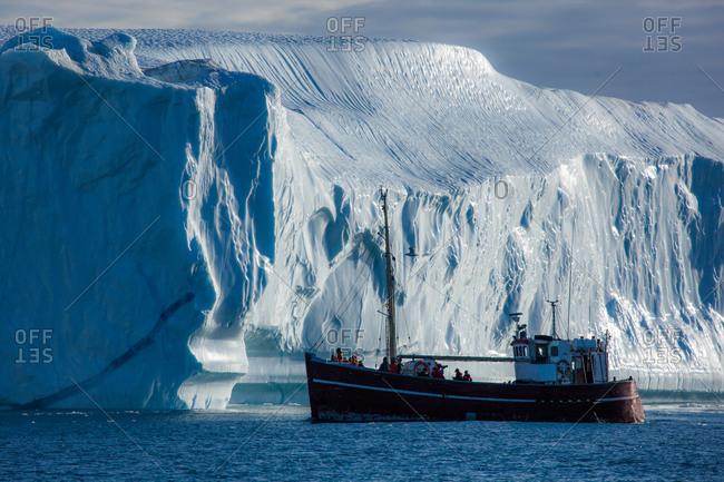 Tour boat next to Iceberg at the Ilulissat Icefjord near Ilulissat, Greenland