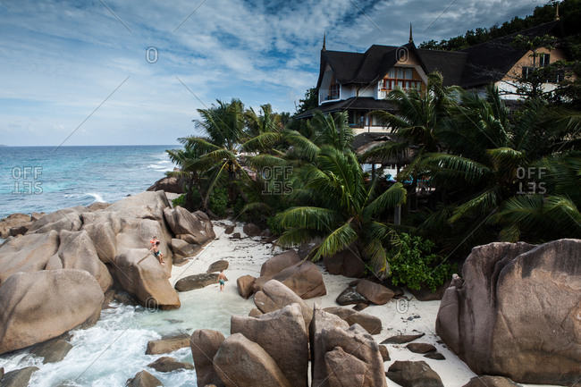 Seychelles, East Africa - December 24, 2016: A boutique hotel on the water front with a family climbing on the rocks, La digue, Seychelles