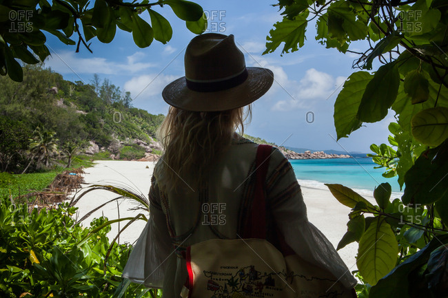 A woman or girl framed between the leaves, looks out at a hidden beach. Seychelles.
