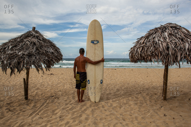 Panama - March 10, 2014: Surfer with longboard standing on beach between two palm umbrellas