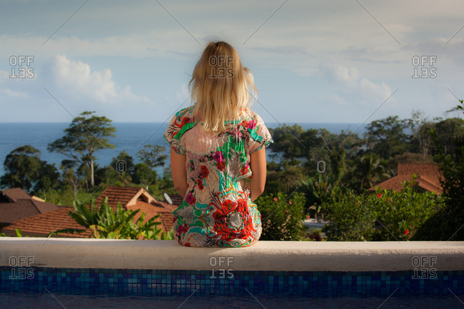 Blonde girl in colorful dress sitting on the pool edge overlooking the ocean, panama, Caribbean