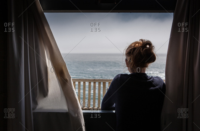 Girl stares out at the ocean from the window.