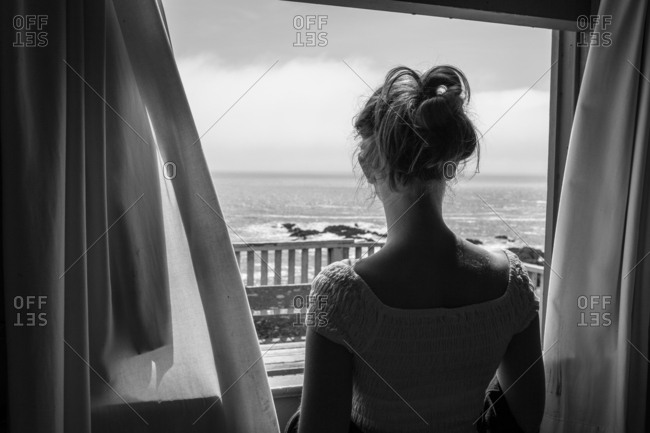 Young girl stares out at the ocean from the window with curtains