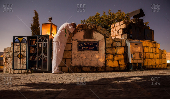 Safed, Israel - July 20, 2013: A Jewish man prays at a holy site in Israel at night