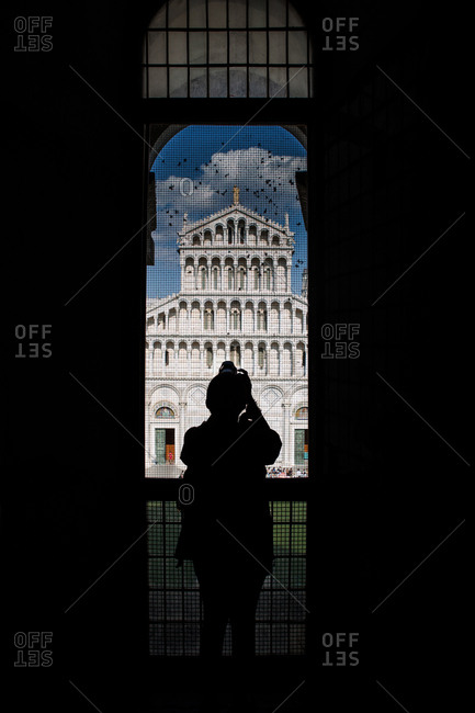 A tourist takes a picture of the Pisa Cathedral