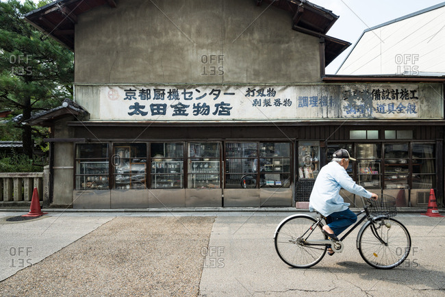 Kyoto, JAPAN - August 13, 2016: Side view of man riding bicycle on street.