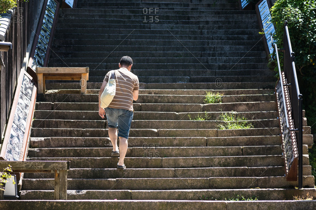 Japanese man walking up stairs.