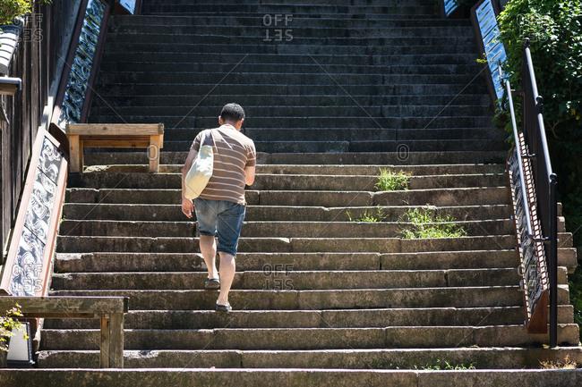 Japanese man walking up stairs.