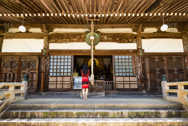 Kobe, JAPAN - August 31, 2016: Japanese woman praying at temple.