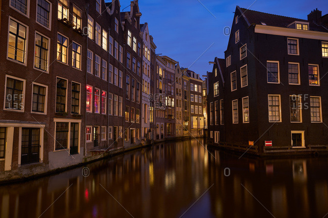 Row houses at night along a canal in Amsterdam