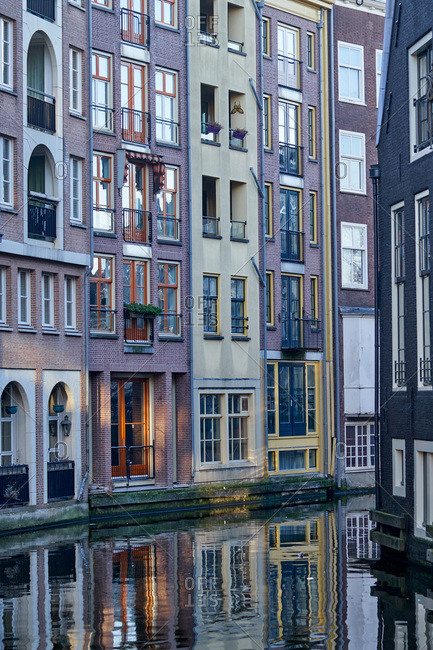 Row houses reflecting in a canal in Amsterdam