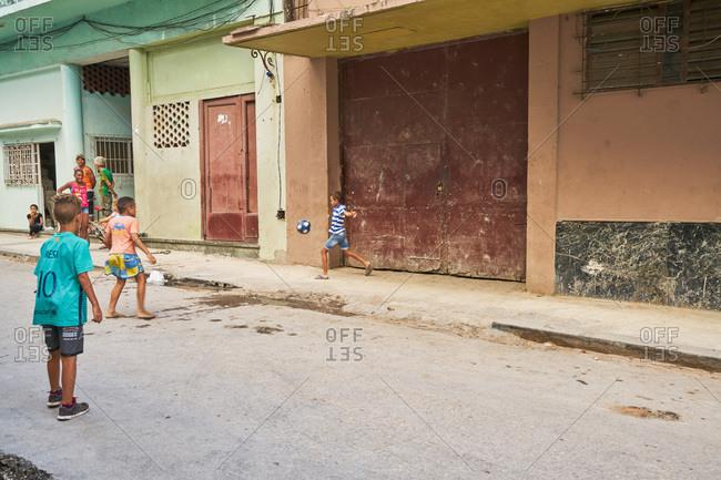 Havana, Cuba - March 3, 2017: Kids playing with soccer ball in the street in Havana, Cuba