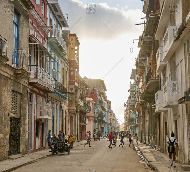 Havana, Cuba - March 3, 2017: People on the street and kids playing with a ball in Havana