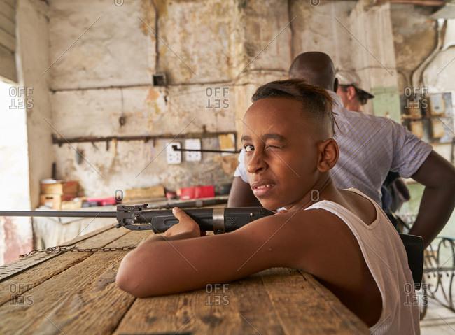 Havana, Cuba - March 4, 2017: Child holding rifle at a gun range