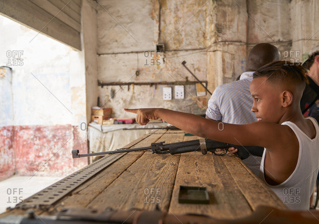 Havana, Cuba - March 4, 2017: Boy pointing and holding rifle at a gun range