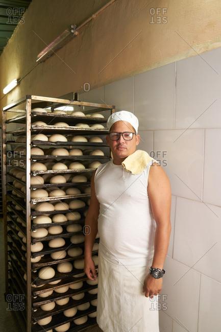 Havana, Cuba - March 5, 2017: Baker standing dough on trays in a bakery