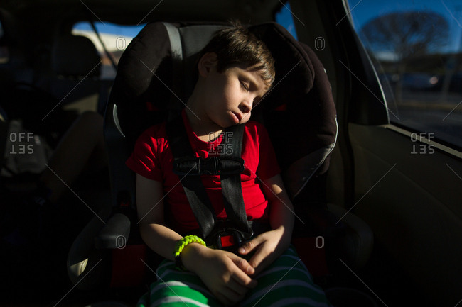 Young boy asleep in a car seat