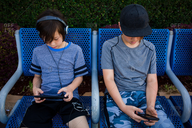 Two boys sitting on blue bench using phones and tablets