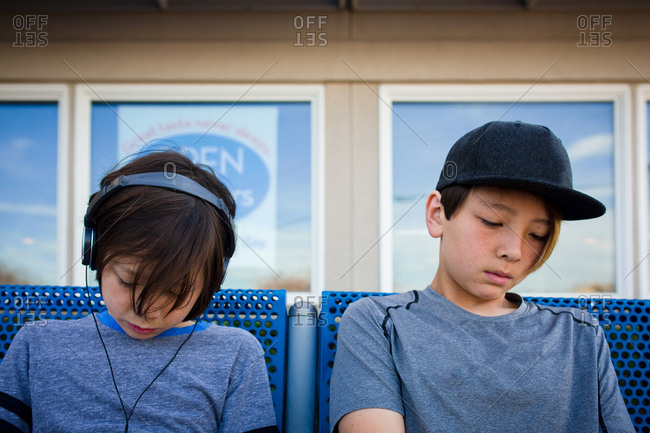 Two boys sitting on blue bench together