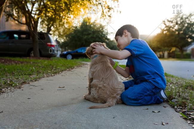 Child petting puppy on sidewalk