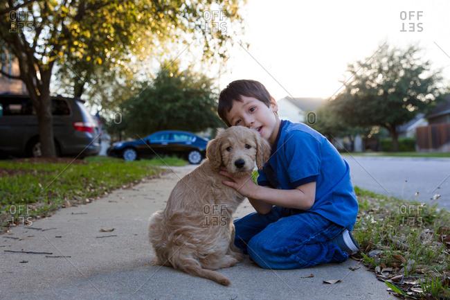 Boy and puppy on sidewalk