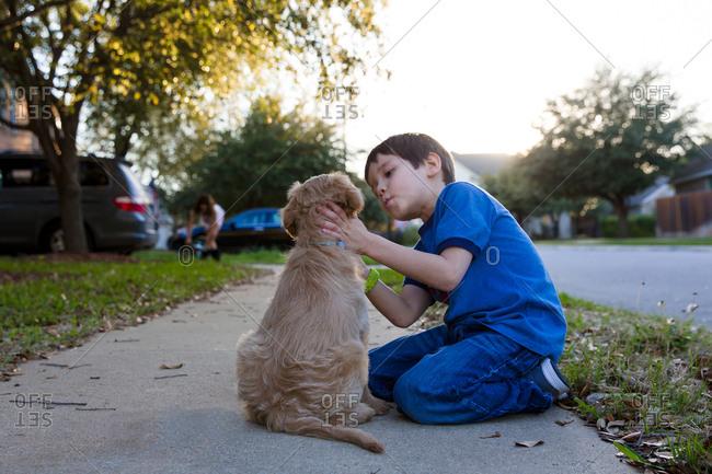 Little boy preparing to kiss puppy on sidewalk