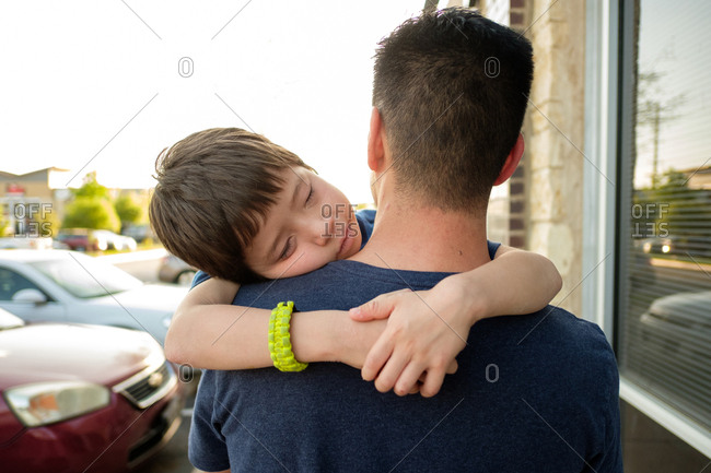 Father carrying sleeping son