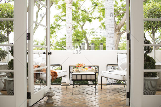 West Hollywood, California, USA - May 5, 2015: French doors in condo open to outdoor dining area on patio