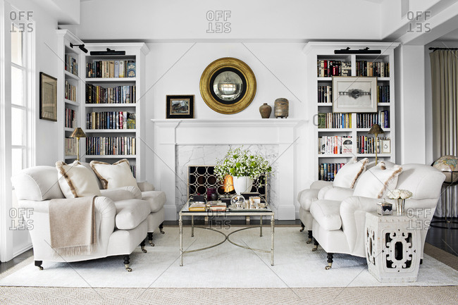 West Hollywood, California, USA - May 4, 2015: Living room of condo with chairs, bookcases, and fireplace