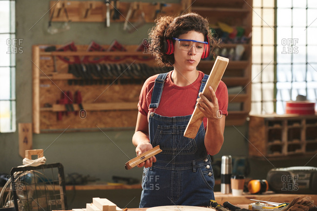 Professional carpenter at work. Young curly woman in protective eyewear, earmuff and denim overall checking quality of processed wooden plank