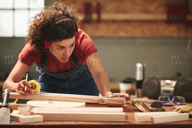 At carpenter workshop. Young concentrated curly woman in ear defenders and overall measuring wooden plank with tape measure