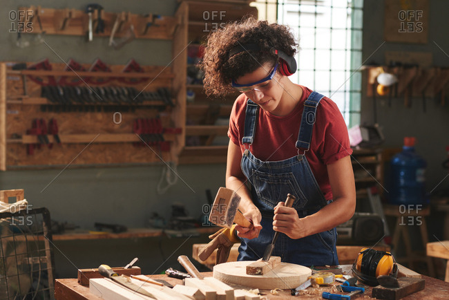 Carpenter in workshop. Concentrated curly woman in ear defenders and goggles using hammer and chisel while working with wooden plank