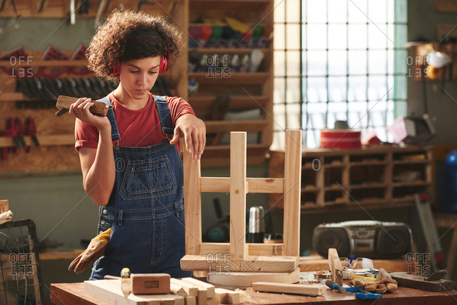 At carpenter workshop. Young curly woman in ear defenders and denim overall holding hand plane and looking at finished wooden stool pensively before polishing it