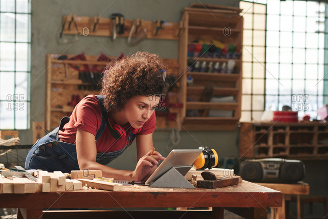 Carpentry for beginners. Young concentrated woman with curly hair reading instructions on digital tablet before working with wood