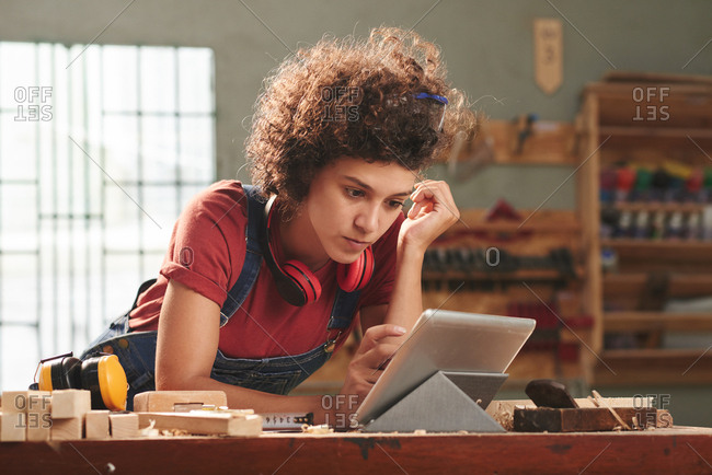 At carpentry workshop. Young curly woman with earmuffs on her neck attentively reading manual on digital tablet before processing wood
