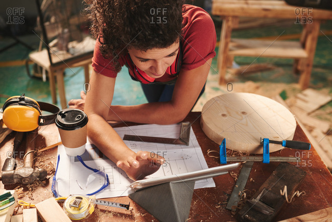 High angle view of young female carpenter reading manual on digital tablet while leaning over table covered with drafts, tool and sawdust