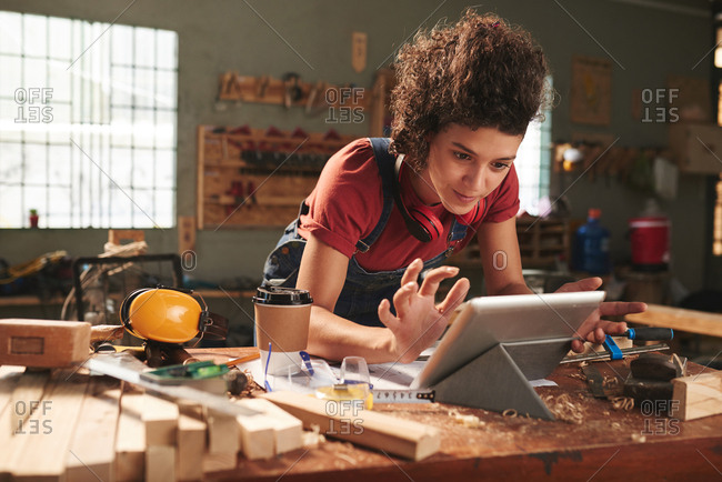 Carpentry for beginners. Young pretty woman with curly hair watching woodworking tutorial on digital tablet while leaning on messy table covered with sawdust