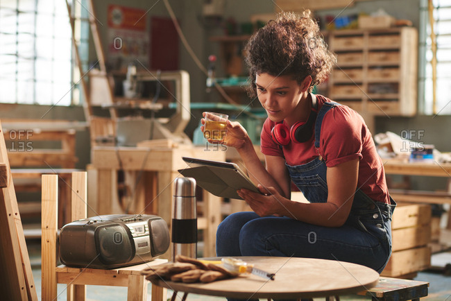 At carpentry workshop. Young pretty female carpenter in denim overall resting on wooden bench with cup of tea and reading book on digital tablet