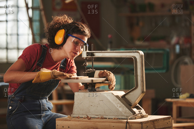 Professional carpenter at work. Young concentrated woman in protective eyewear and earmuffs making holes in wooden plank with drill press