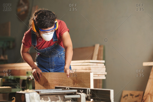 Professional carpenter at work. Concentrated woman in denim overall, protective eyewear and earmuffs processing wooden plank on woodworking machine