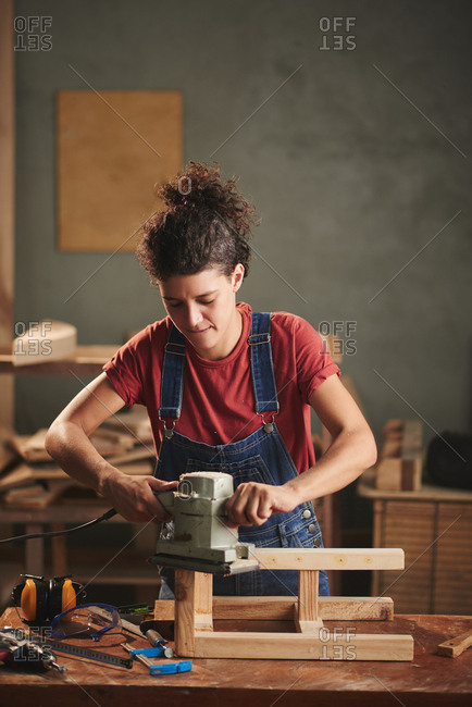 At carpentry workshop. Young curly woman in denim overall enjoying process of smoothing wooden stool surface with electrical belt sander