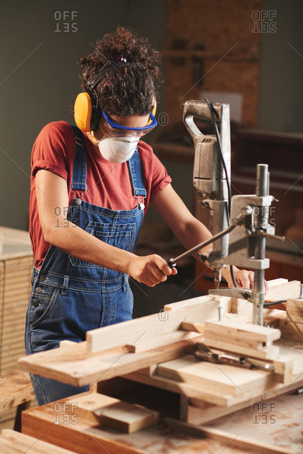 Woodworking industry. Young female carpenter in protective eyewear and ear defenders pressing lever on woodworking machine while cutting wooden planks