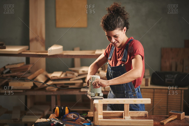 In love with woodworking. Young pretty female carpenter carefully smoothing wooden stool with electrical belt sander and smiling