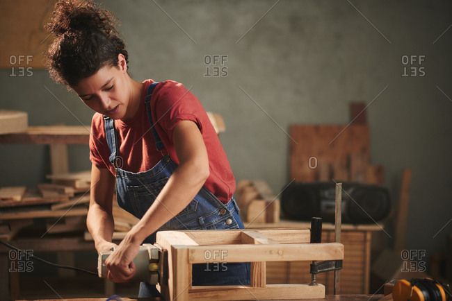 Professional carpenter at work. Young concentrated woman in denim overall smoothing just finished wooden stool with electrical belt sander