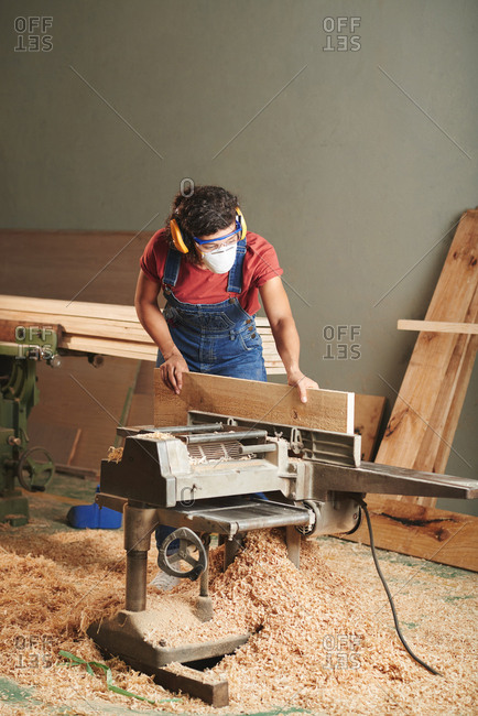Carpentry and joinery. Professional female carpenter in protective eyewear, earmuffs and mask processing wooden plank on woodworking machine. Floor is covered with sawdust